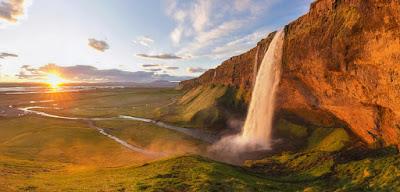 Sol de medianoche en Islandia con una cascada en primer plano