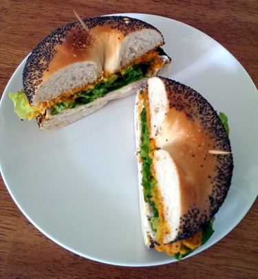 Thanksgiving leftovers bagel with chicken, sweet potato, cream cheese, and greens