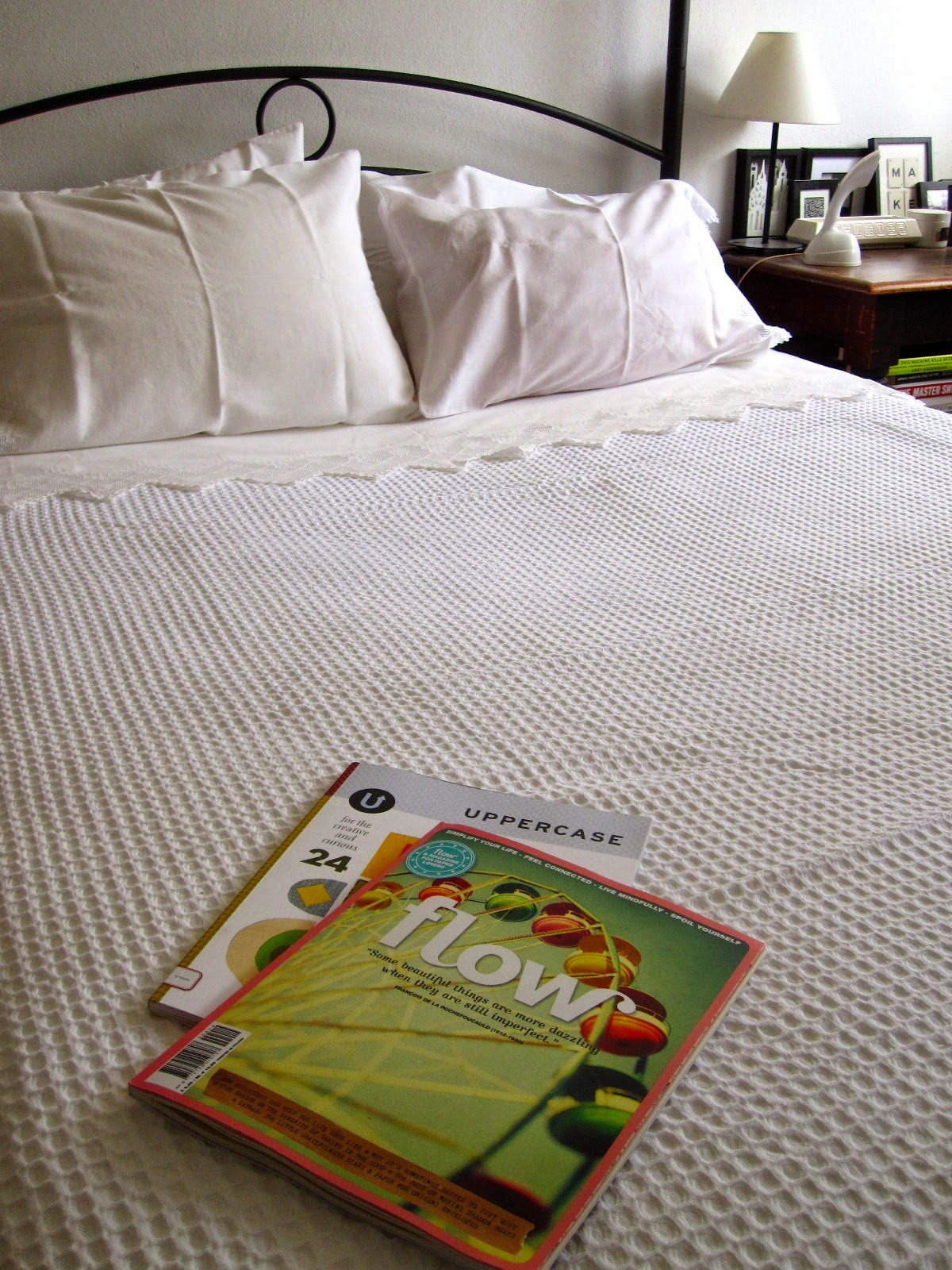 Freshly-made bed with a white waffle-weave blanket and a copy of Flow magazine and Uppercase magazine on it.