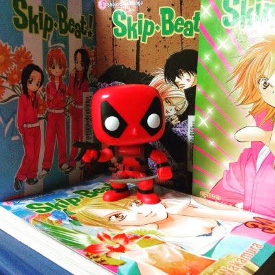 Tiny Deadpool, a bobblehead dressed in a face-covering red costume and brandishing a gun and a katana, stands inside a cave made of Skip Beat. Each of the four volumes features a red-haired Japanese girl on its cover. In one instance, she's accompanied by two other Japanese girls; in another, she snuggles up to a Japanese man.