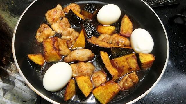 フライパンに調味料とかぼちゃ、鶏にもと茹で卵を入れて煮込む