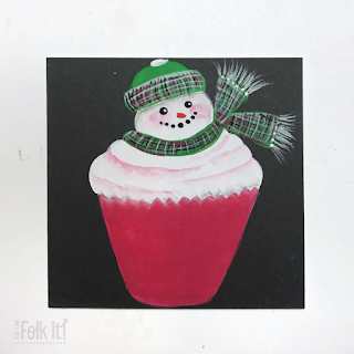 Handpainted snowman topped cupcake design. The snowman is dressed in a green tartan hat and scarf to compliment the red festive cupcake wrapper.