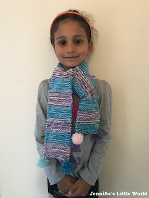 Child wearing a hand knitted pom pom scarf