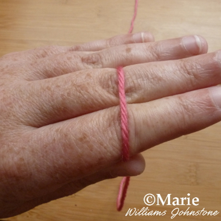 Hand holding red pink yarn between thumb and forefinger