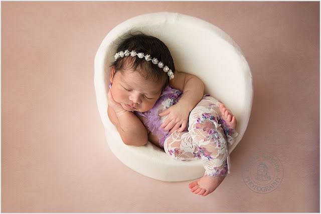 Newborn baby girl in the white chair.