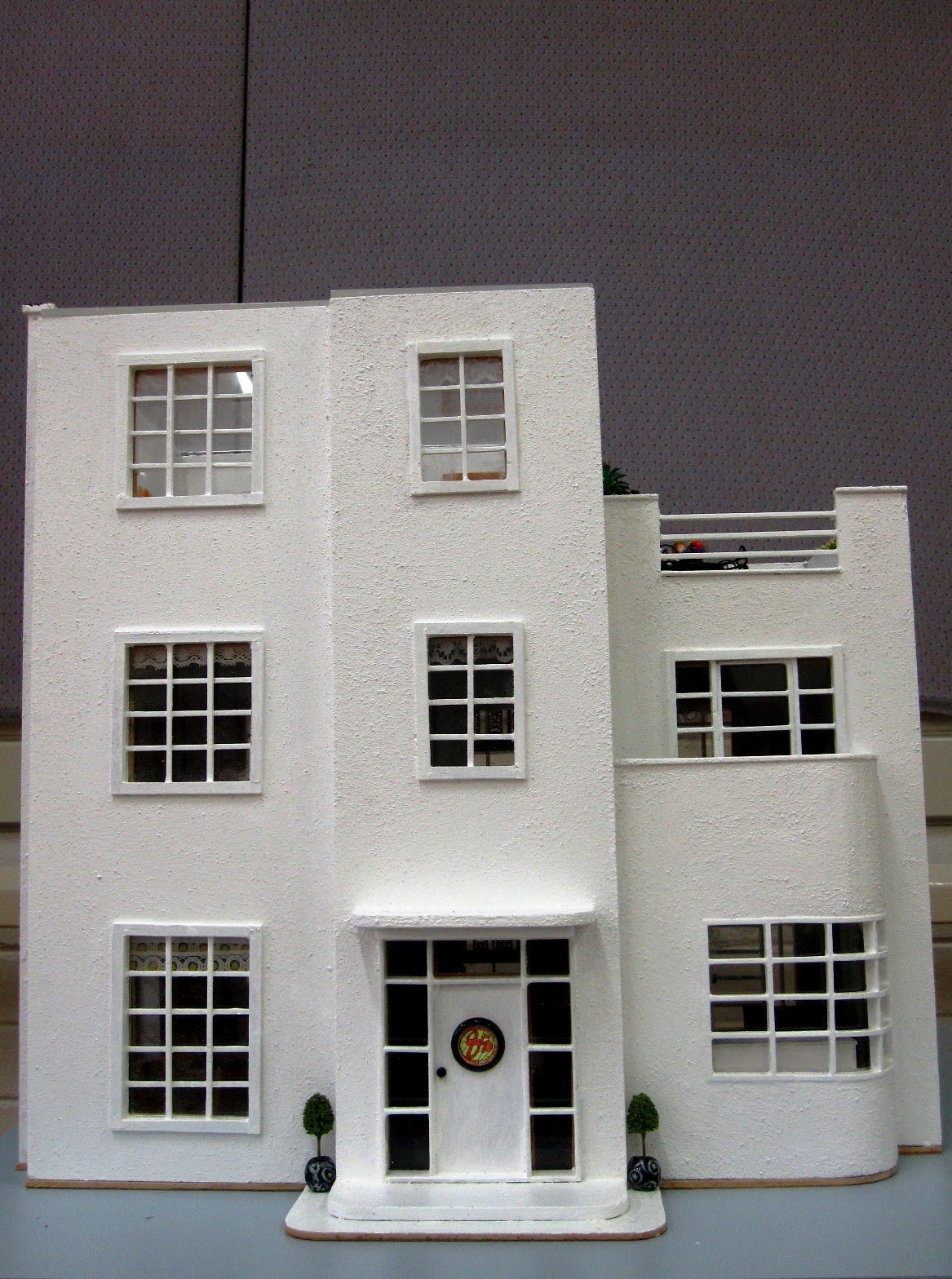 Front of an Art Deco moderne-style dolls house by Anne Reid