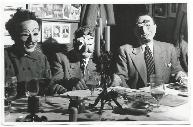 Drei maskierte Herren an einer Tafel