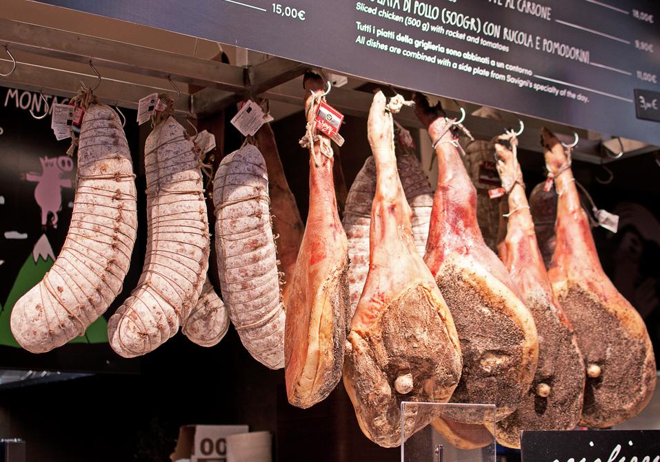 Jambons et saucissons qui pendent sur un étal du mercato centrale de firenze
