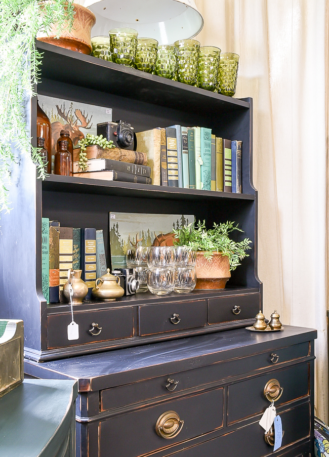 Vintage black hutch styled with blues, greens and amber vintage decor