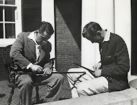 A photograph of two seated men bending over canes and whittling at them.