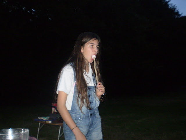 eating a toasted marsh mallow on a stick