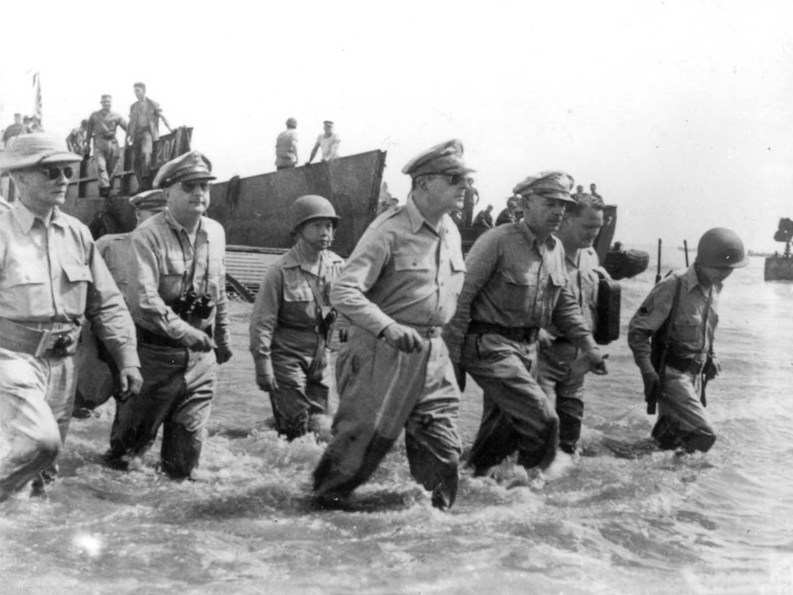 Gen. Douglas MacArthur, center, is accompanied by his officers and Sergio Osmena, president of the Philippines in exile, extreme left, as he wades ashore during landing operations at Leyte, Philippines, on October 20, 1944, after U.S. forces recaptured the beach of the Japanese-occupied island.