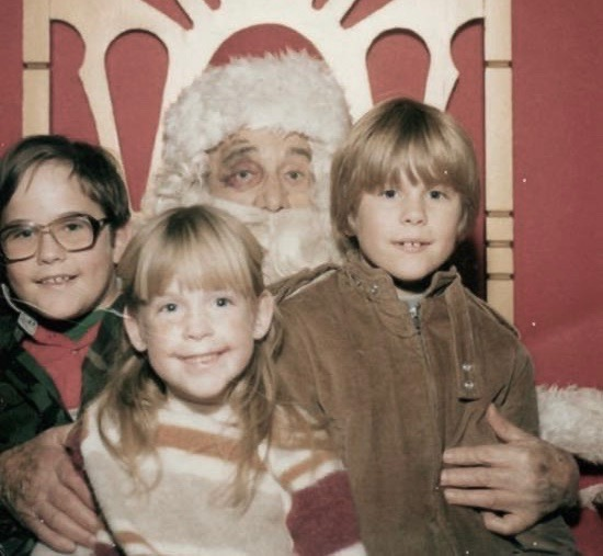 Two brothers and their sister sit on Santa's lap. Santa has a black eye. c.1980s. A Pleasant Christmas Story and other stories of Christmas Creepers. marchmatron.com