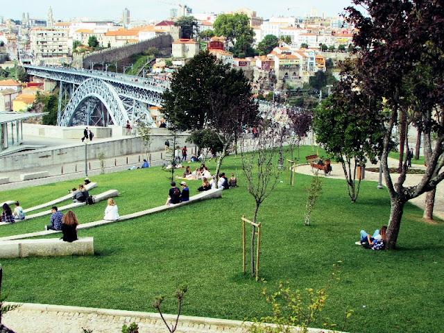 pessoas sentadas no Jardim do Morro com vista para a ponte Luiz I