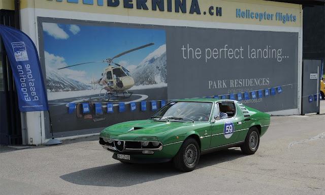 Grüner Alfa Romeo Montreal vor Plakat des Heli Ports im Engadin, Passione Engadina