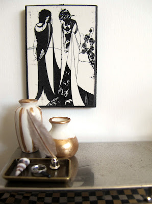 Art deco style modern miniature silver sideboard with a black and white picture hung above it and a selection of white and gold items displayed on it.