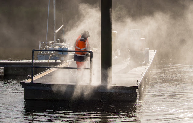 Photo of one of the marina staff pressure washing the pontoons