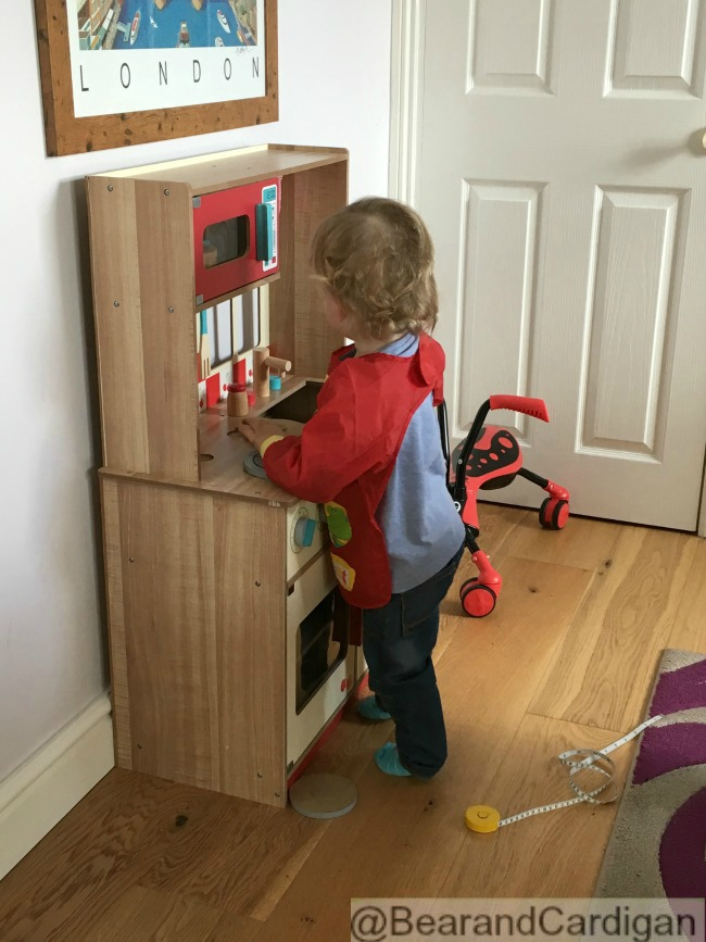 toddler waiting next to play kitchen