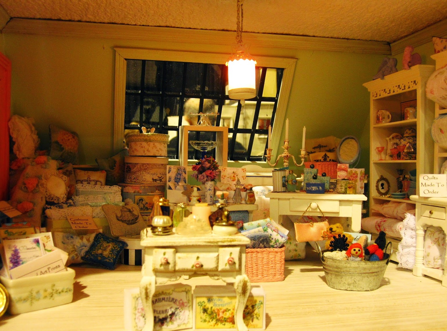 Third floor of a modern miniature shabby chic shop, with a display of soft furnishings and furniture.
