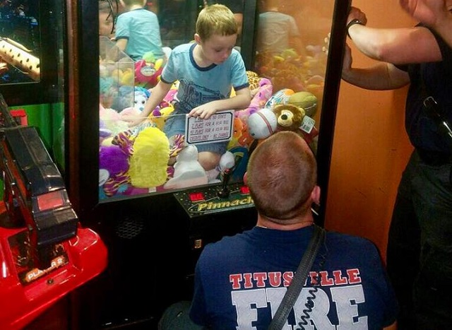 boy stuck in a claw toy vending machine