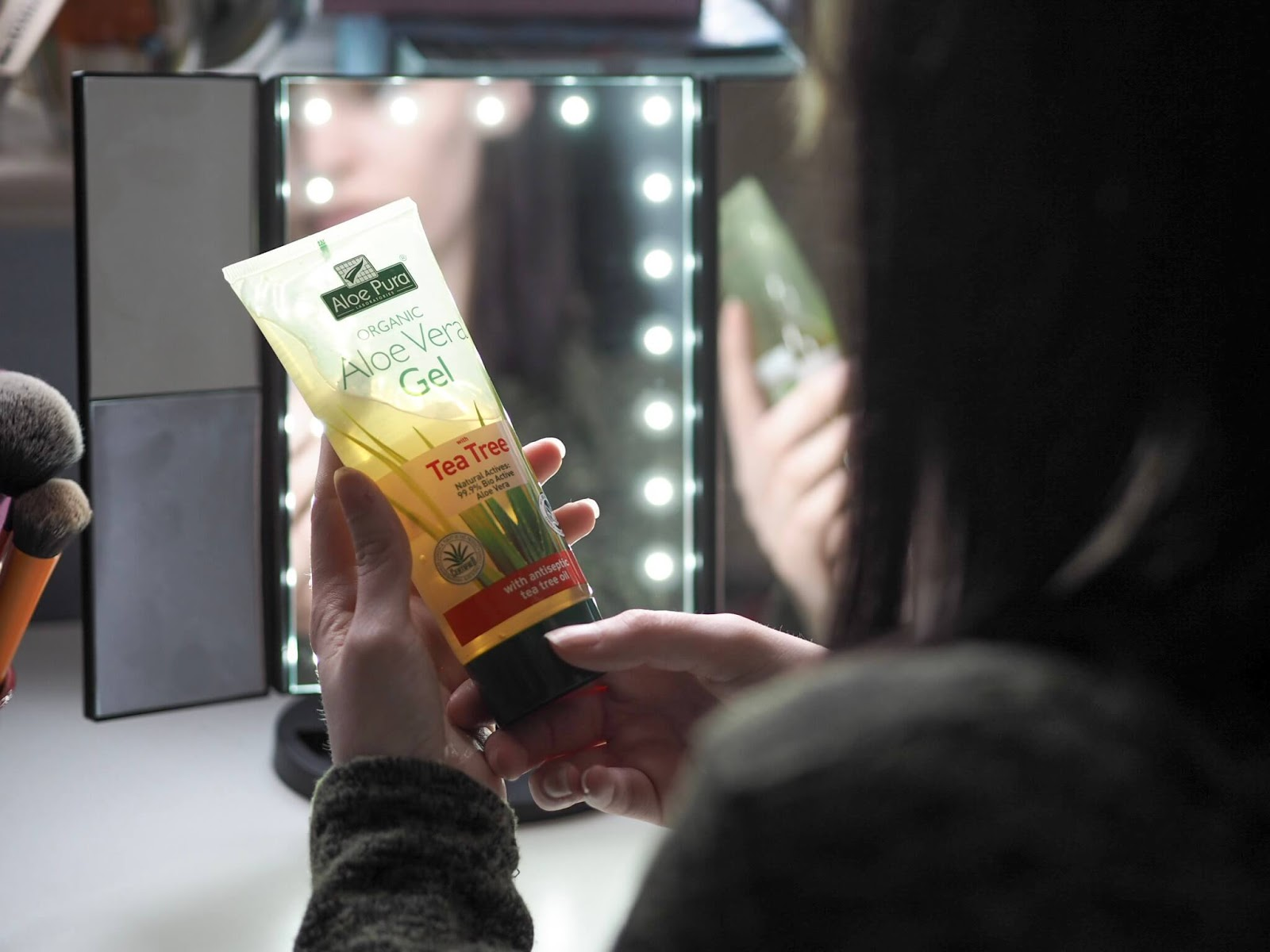Lucy holding Aloe Vera gel near mirror