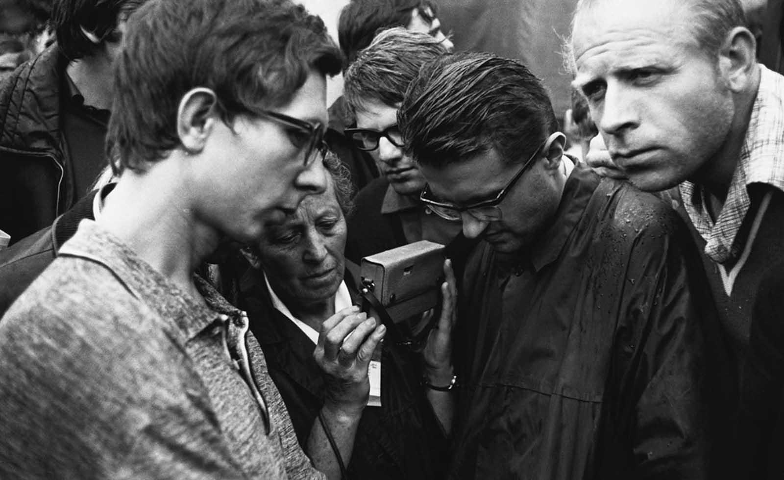 Los checoslovacos se reúnen para escuchar una radio de transistores en busca de noticias de la invasión y ocupación soviética el 29 de agosto de 1968.
