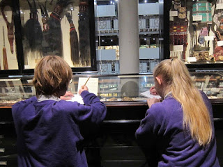 Photograph of two students drawing in the Pitt Rivers Museum