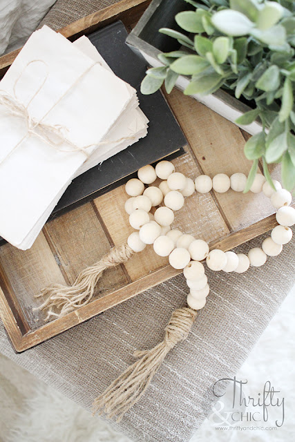 wood bead garland on tray with books