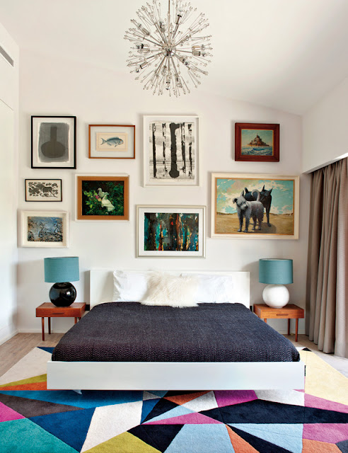 Bold bedroom white headboard low bed graphic print rug wall covered in pictures modern chandelier