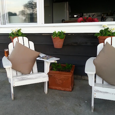 Two adirondack chairs on a holiday house porch.