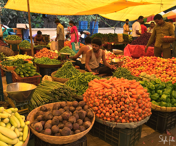 Image of a vegetable vendor sitting in a market selling carrots, beetroots, capsicum and cucumbers in Goa