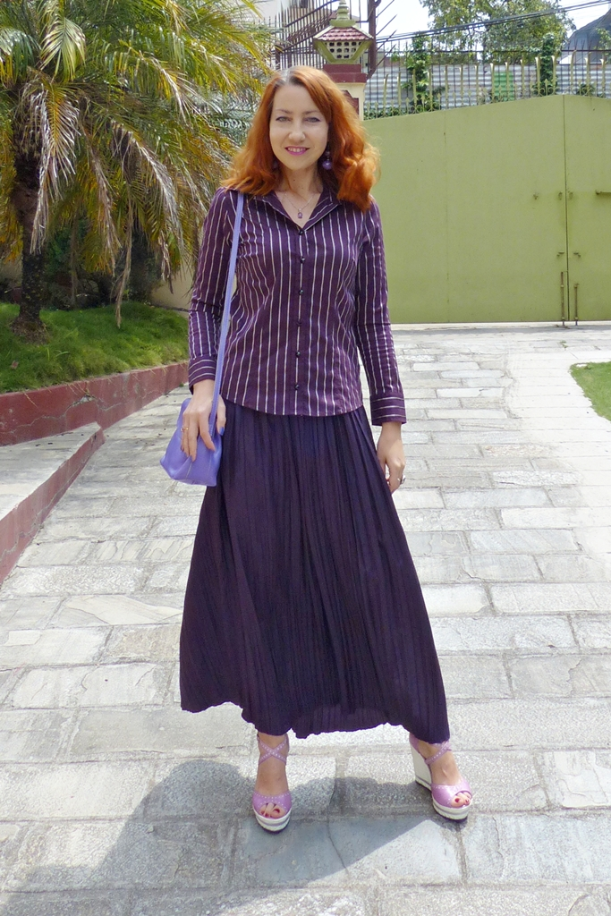 Pleated silk skirt worn in semi-casual way with a shirt and wedges