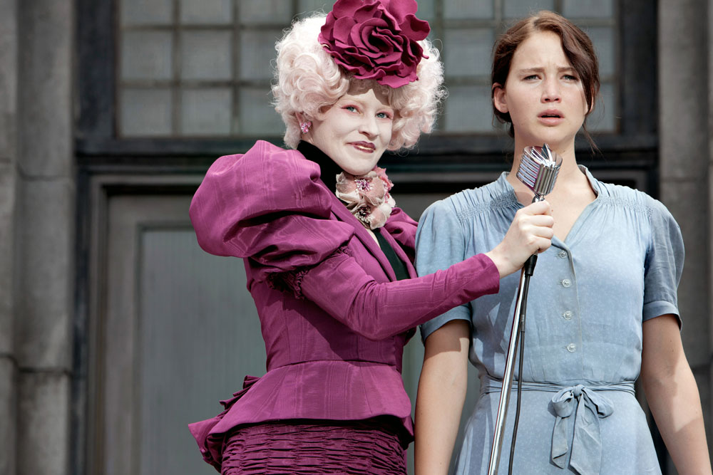 Katniss Everdeen, young brunette woman in plain light-blue dress, next to Effie Trinket, smirking woman in pale powdered white wig and bright pink or maroon ornate dress