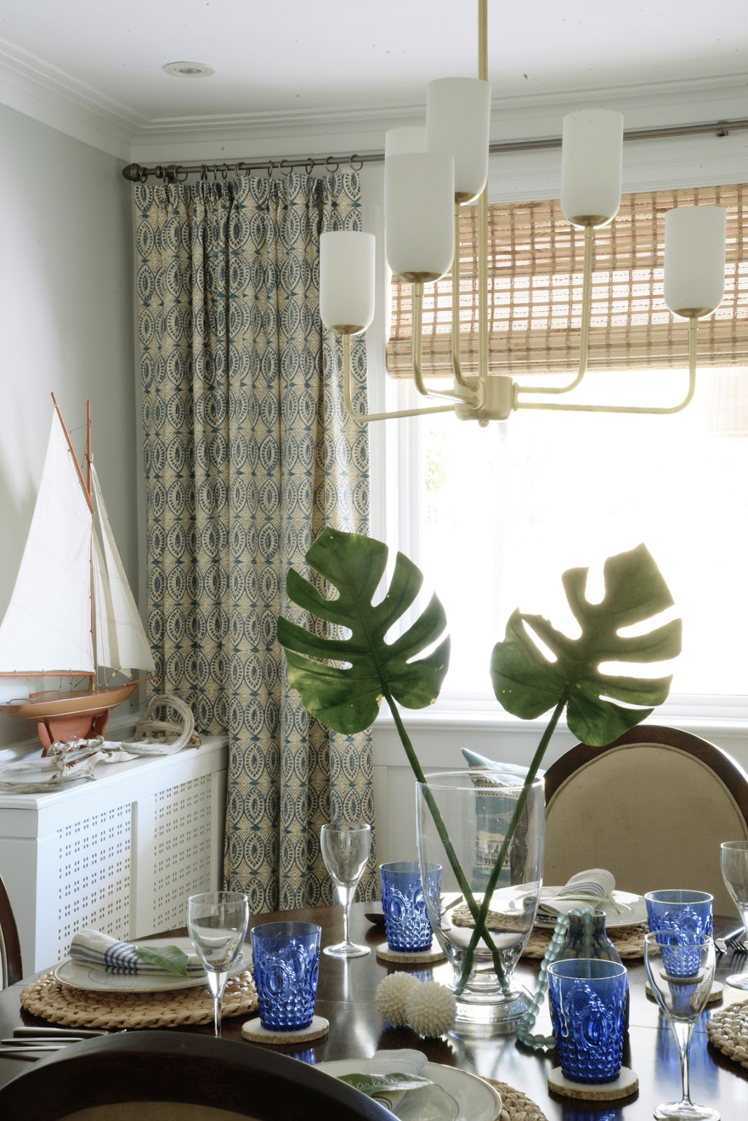 Rambling Renovators | tropical dining room, gold chandelier, split leaf philodendron, sailboat