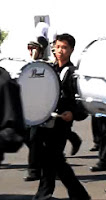 teenager marching in band playing bass drum