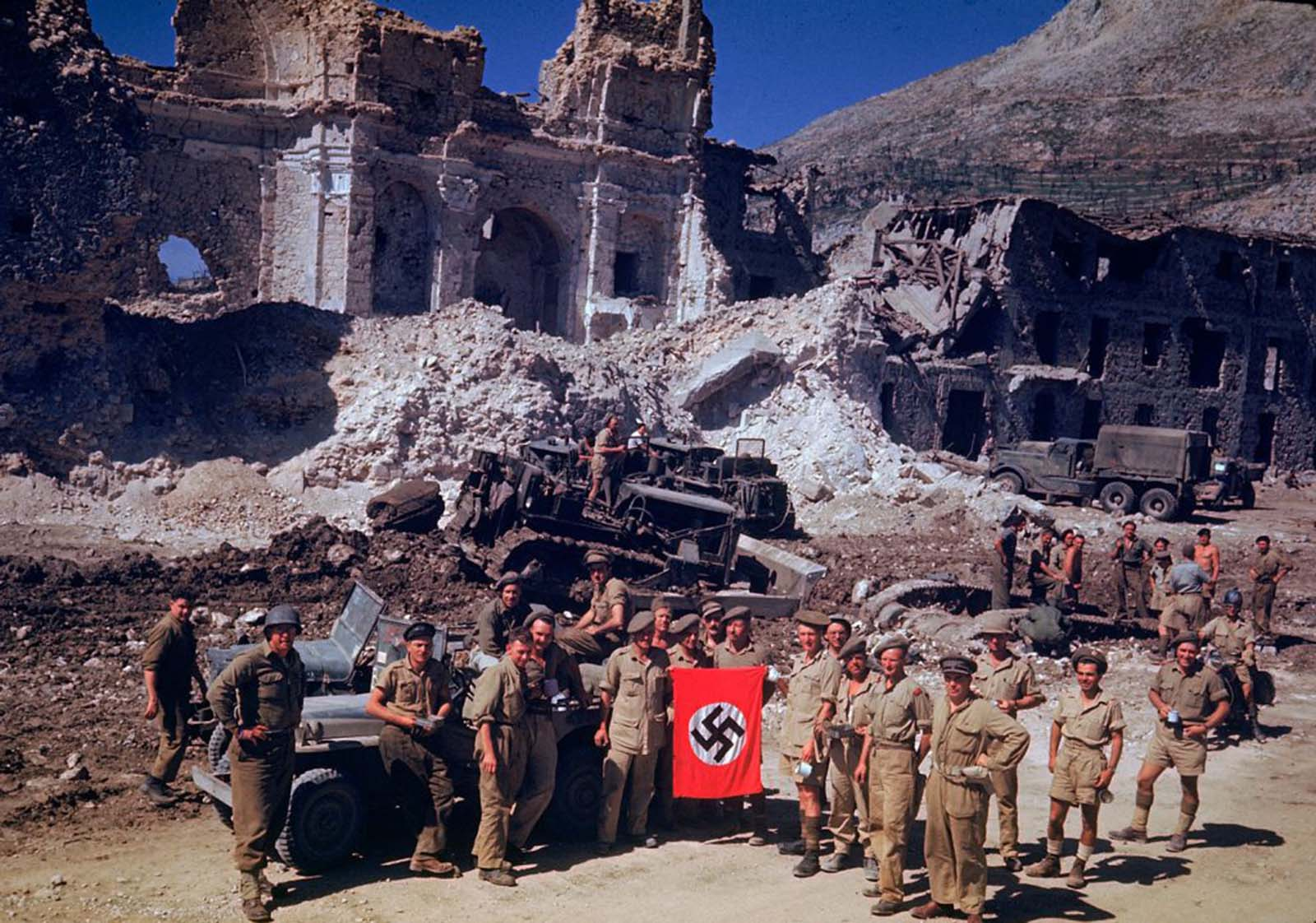British and South African soldiers held up a Nazi trophy flag while combat engineers on bulldozers cleared a path through the debris of a bombed-out city, Italian Campaign, World War II.