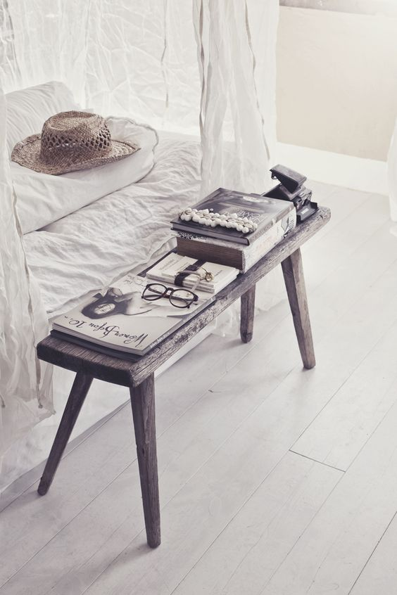 Rustic bench at end of bed with white linens, photo by Hanna Lemholt