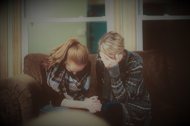 two women sitting on a sofa and praying together