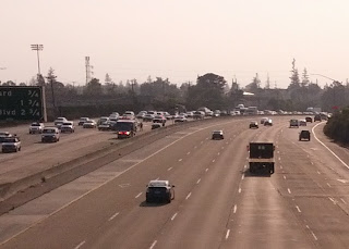 Ambulances and police officers respond to rush hour freeway traffic collision.