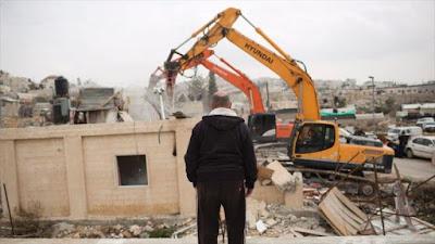 Un hombre palestino observa cómo las fuerzas del régimen israelí destruyen su casa.
