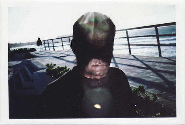dirty photos - Once - street photo of man with shadow black face and lens flare