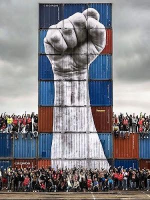Grafiti del artista JR de un puño pintado sobre una torre de contenedores portuarios