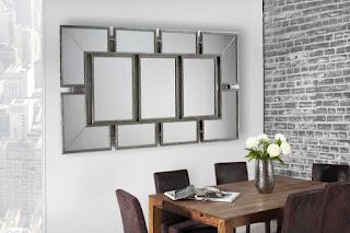Nástenné zrcadlo v stříbrnej barvě.