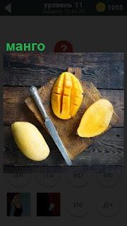 На разделочной доске манго разрезаны ножом на несколько частей