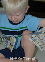 little boy shredding newspaper