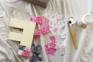 a wooden letter 'f' sits next to torn strips of navy, white, and pink, floral tissue paper, and a brush with an open pot of mod podge; the wooden letter is in the process of being covered