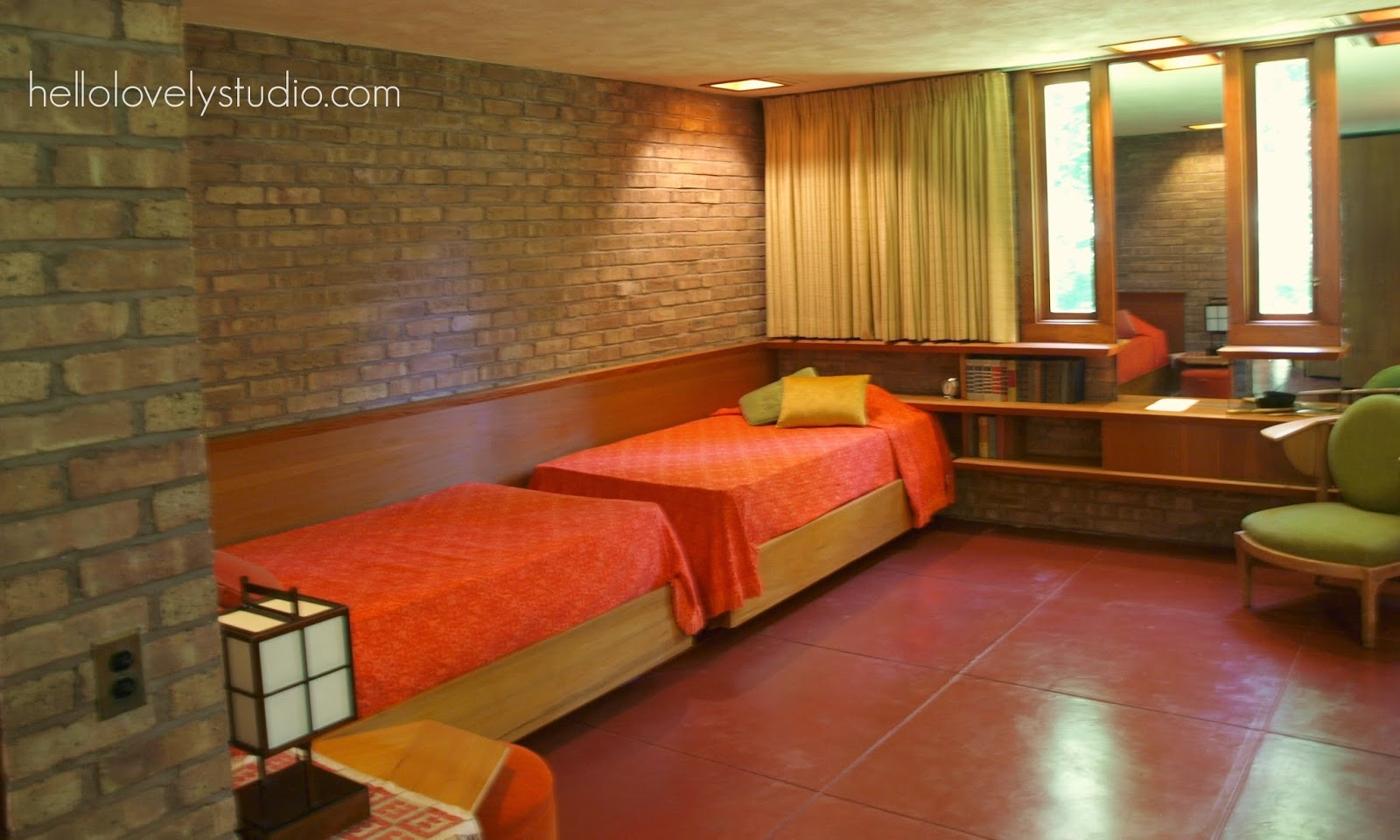 Bedroom with twin beds and orange bed linens. Frank Lloyd Wright Laurent House designed for owner Kenneth Laurent on Spring Brook Road in Rockford/ Designed to be wheelchair-accessible. #flw #franklloydwrighthouse #midcenturymodernarchitecture
