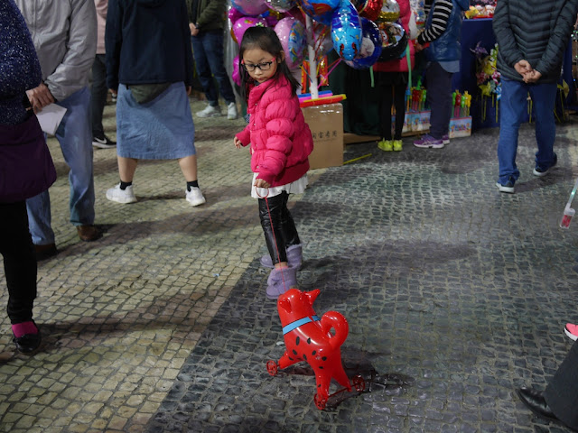 girl pulling inflatable dog on wheels