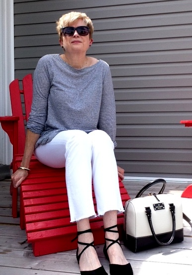 woman in grey striped top, white jeans, black flats sitting in red Adirondack chair