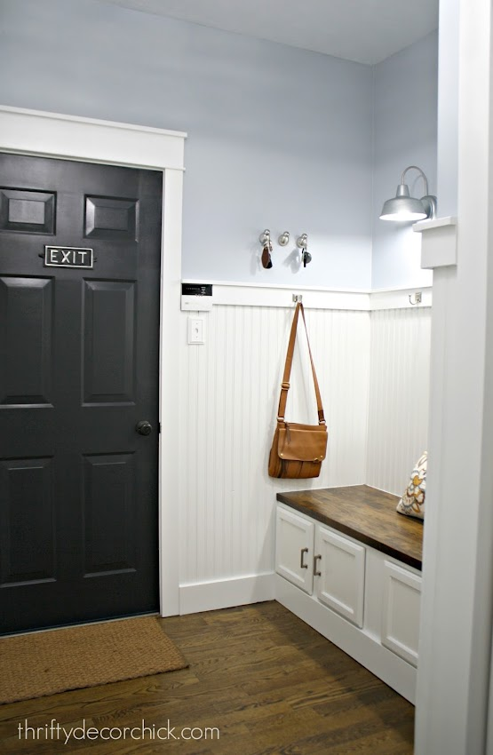 black door white trim blue walls in mudroom